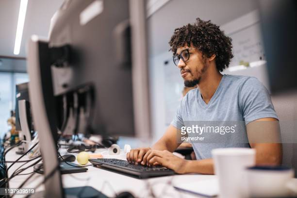 young african american programmer working on desktop pc in the office. - coding stock pictures, royalty-free photos & images