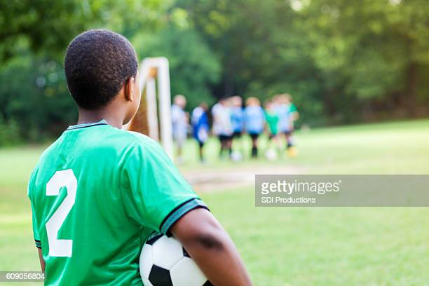 young african american soccer player waits to play in game - sideline stock pictures, royalty-free photos & images