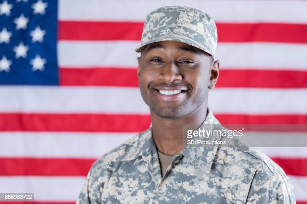 Young African American soldier stands confidently in front of flag