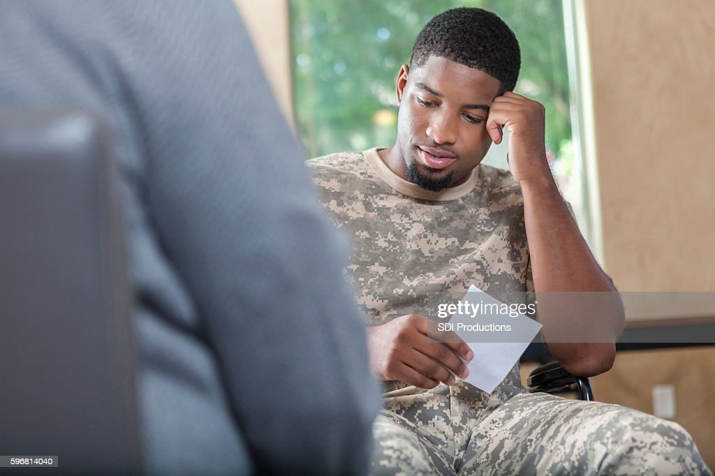 Young African American soldier talking to counselor about prescription : Stock Photo