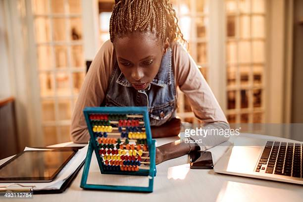 Young African American woman calculating something on abacus.