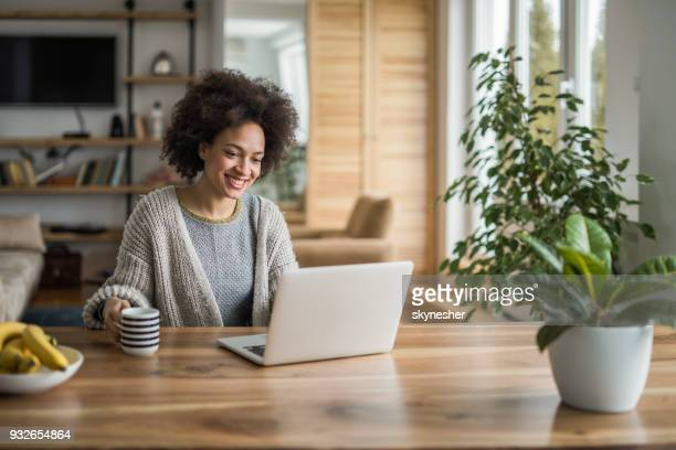 Young African American woman drinking coffee and using laptop at home.