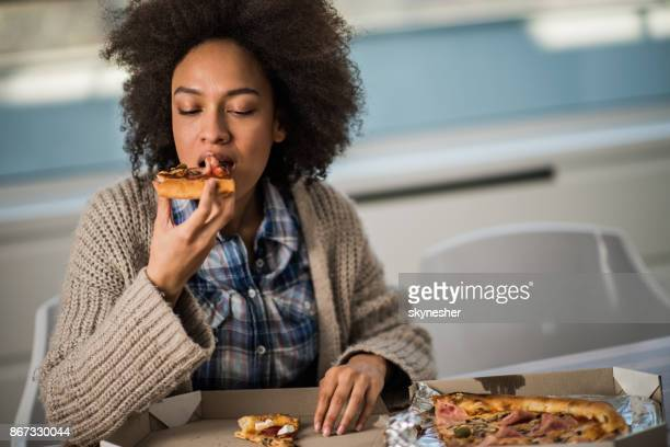 Young African American woman eating pizza at home.