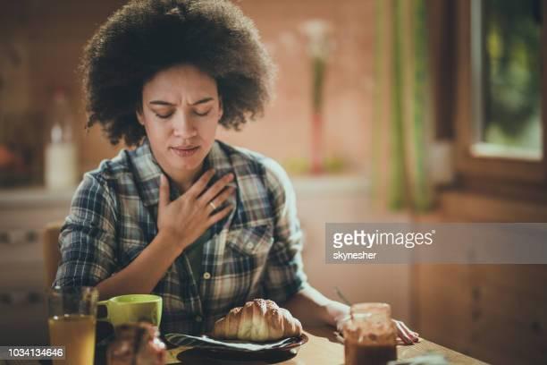 jonge african american vrouw gevoel misselijkheid tijdens ontbijt eetkamer. - afkeer stockfoto's en -beelden