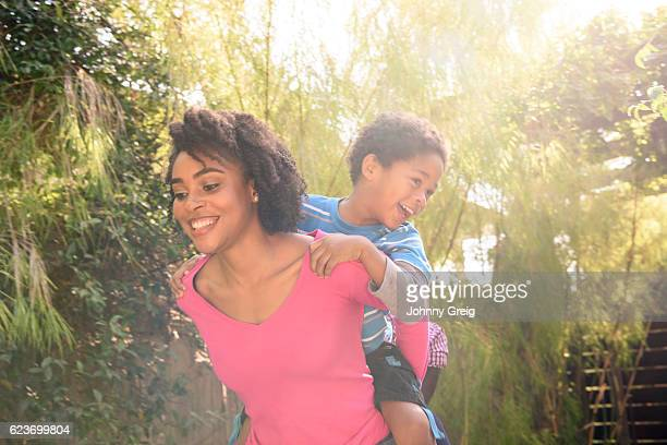 Young African American woman giving son piggy back in garden