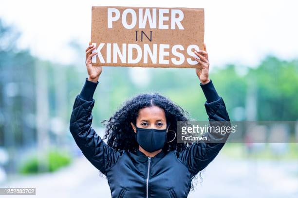 young african american woman holding protest sign - protestor stock pictures, royalty-free photos & images