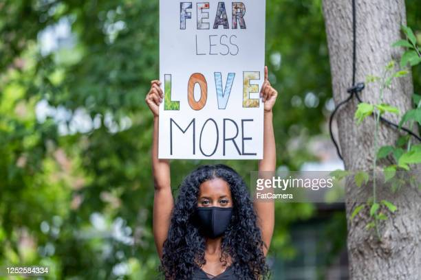 young african american woman holding protest sign - black civil rights stock pictures, royalty-free photos & images