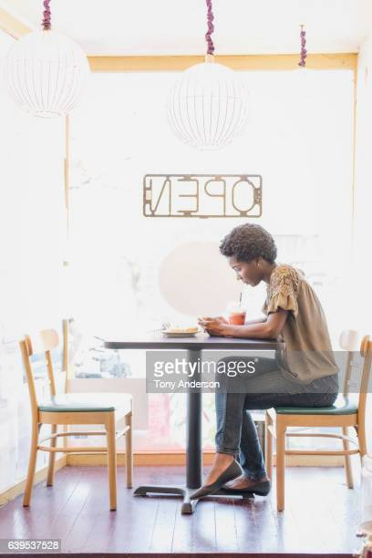 young african american woman in cafe sitting near window with pastry and beverage looking at her phone - open blouse stock photos and pictures