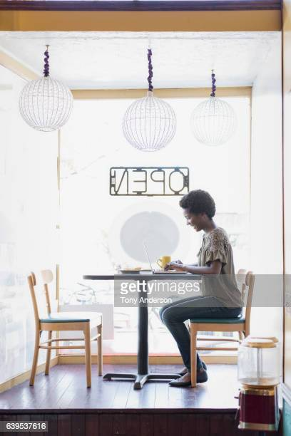 young african american woman in cafe with phone - open blouse - fotografias e filmes do acervo