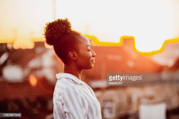 young african american woman is relaxing on the rooftop - mental health stock pictures, royalty-free photos & images