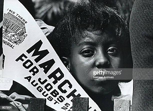 Young African American woman listens during a civil rights rally at the Lincoln Memorial August 28, 1963 in Washington.