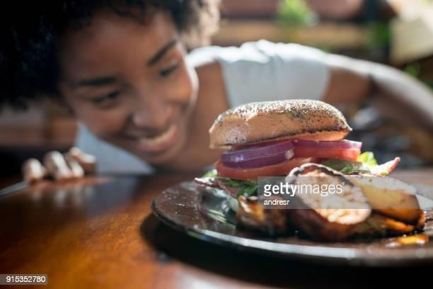 Jeune femme afro-américaine en regardant son burguer se penchant sur la table
