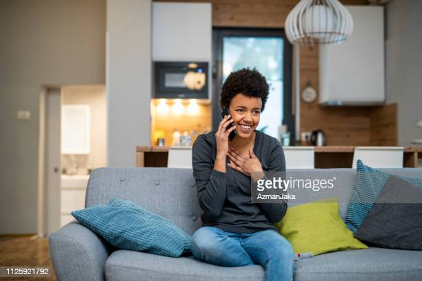 young african american woman making a phone call and sitting on the sofa - relief emotion stock pictures, royalty-free photos & images