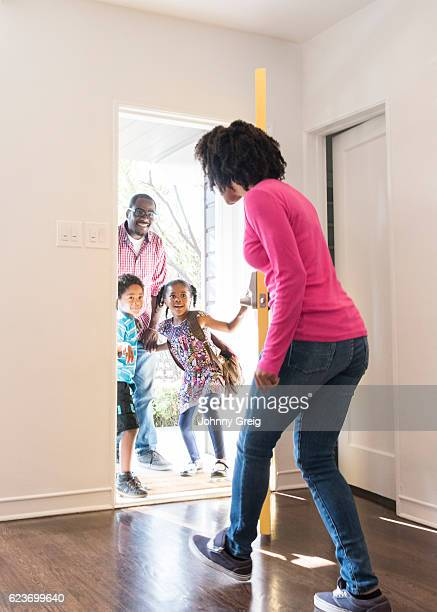 Young African American woman opening door to family