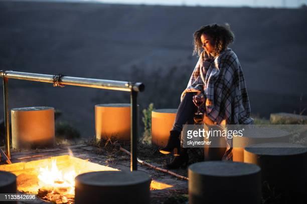 junge afroamerikanerin sitzt allein nachts am feuer - holzfeuer stock-fotos und bilder