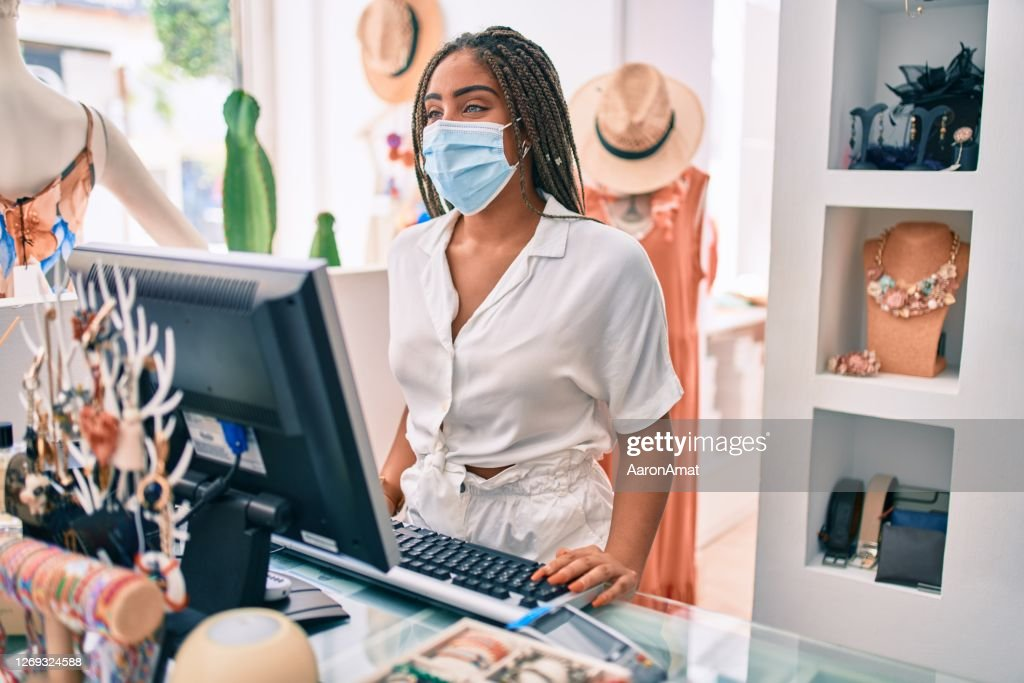 Young african american woman smiling happy working at the till wearing coronavirus safety mask at retail shop : Stock Photo