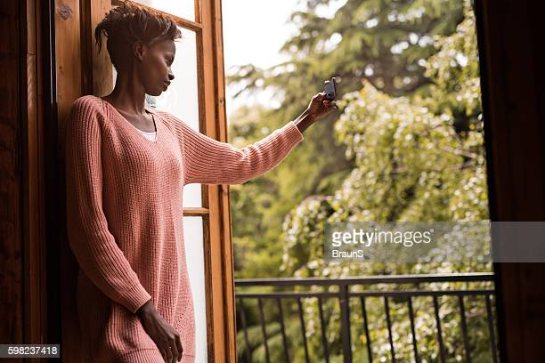 Young African American woman taking a selfie with cell phone.
