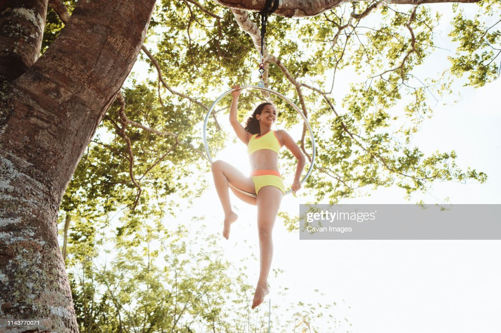 Young African American Woman Training With Aerial Hoop Hanging on Tree : Stock Photo