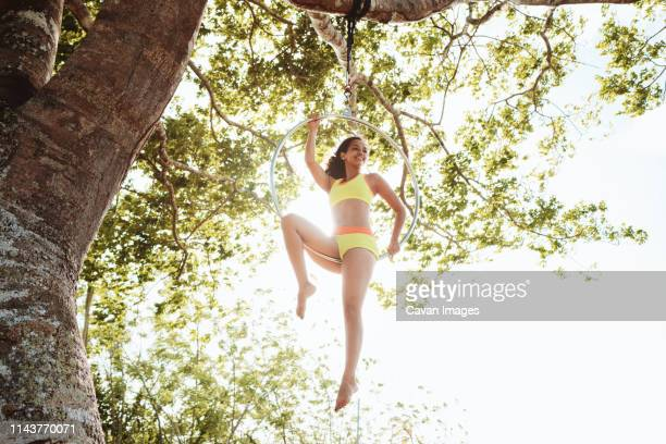 Young African American Woman Training With Aerial Hoop Hanging on Tree
