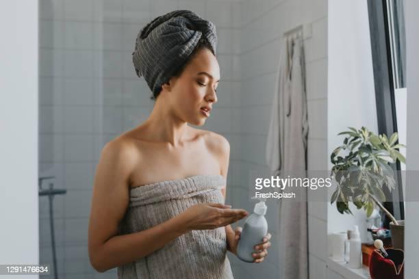 jovem afro-americana enrolada em uma toalha após um chuveiro segurando um produto de cuidados com a pele - só uma mulher de idade mediana - fotografias e filmes do acervo
