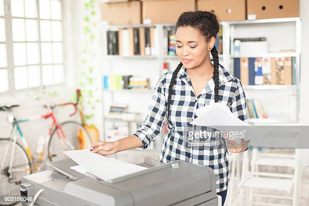 Young african assistant using copy machine at workplace