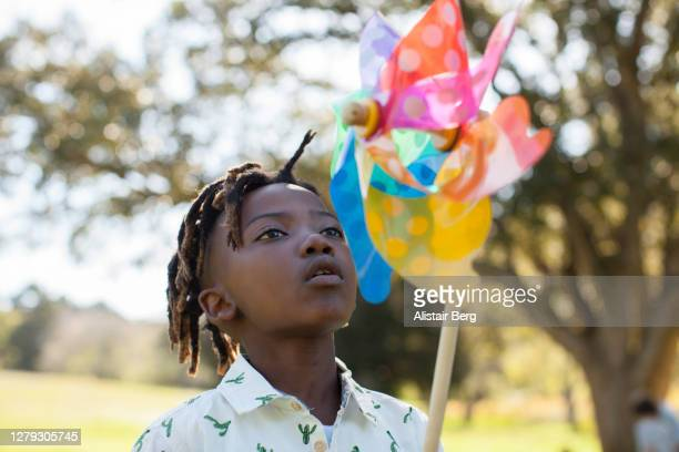 young african boy blowing windmill in nature - africa stock pictures, royalty-free photos & images
