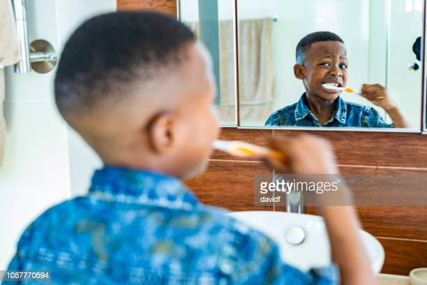 young african boy brushing his teeth - brushing teeth stock pictures, royalty-free photos & images