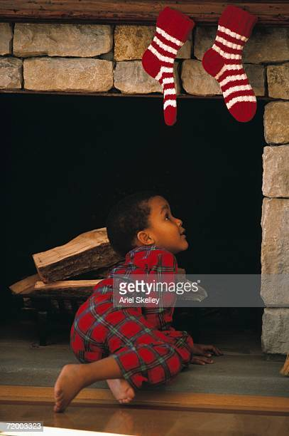 young african boy looking up chimney with stockings hanging on it - stockings no shoes stock pictures, royalty-free photos & images