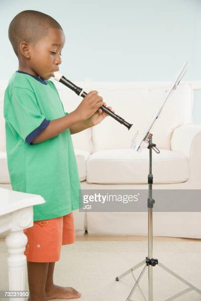young african boy playing a recorder with sheet music - recorder musical instrument stock photos and pictures