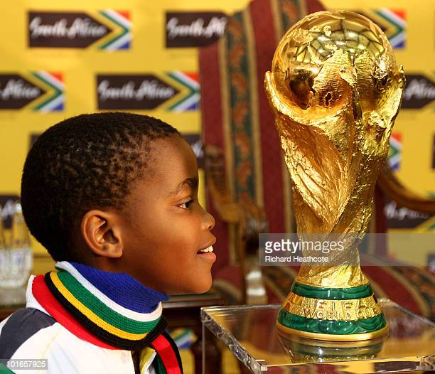 Young African boy poses next to the trophy before the South Africa's President Zuma and FIFA President Blatter FIFA World Cup press conference at the...
