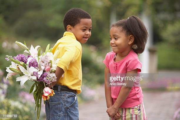 Young African boy surprising young African girl with flower bouquet