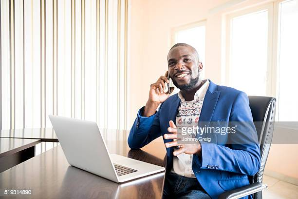 Young African businessman on mobile phone in office