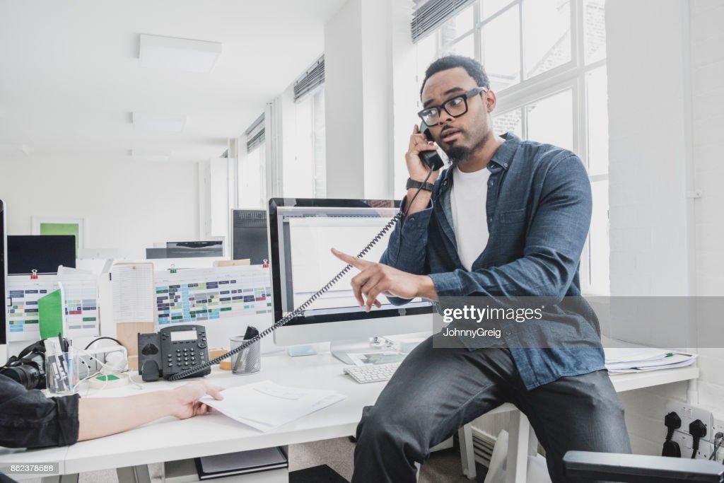 Junge afrikanische Unternehmer sitzen am Schreibtisch mit Telefon und zeigt : Stock-Foto