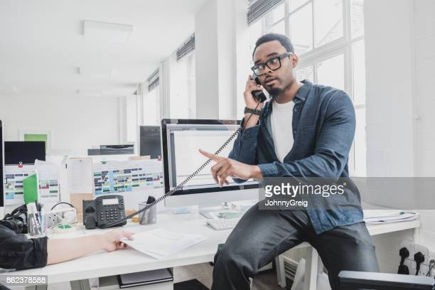Young African businessman sitting on desk using phone and pointing