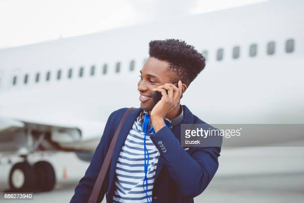 Young african businessman using mobile phone on airport