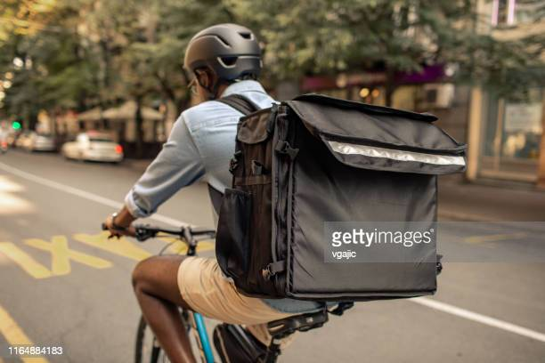 young african delivery man riding bicycle in the city - delivery person stock pictures, royalty-free photos & images