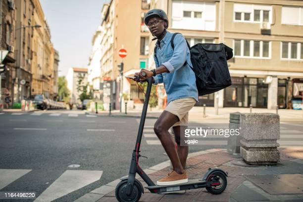 young african delivery man riding electric scooter in the city - scooter stock pictures, royalty-free photos & images