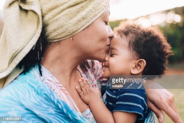 young african descendant mother kissing her baby son on the forehead - mixed race person stock pictures, royalty-free photos & images