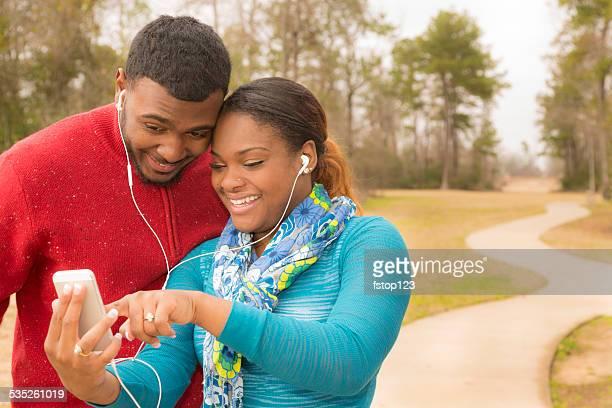 Junge afrikanische Herkunft paar Musik hören. Smartphone. Funktioniert.