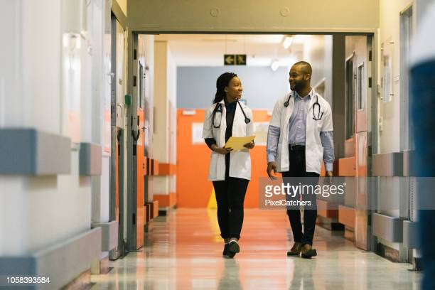 young african doctors walking down hospital corridor talking - medical building stock pictures, royalty-free photos & images