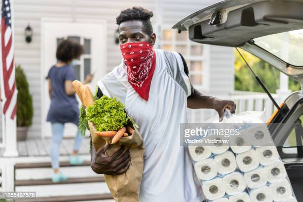 young african ethnicity man unloading grocery bags and toilette paper after arriving from shopping at moment of virus pandemic - bandana stock pictures, royalty-free photos & images