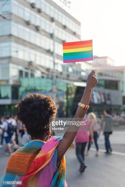 愛の祭典で虹のプライドの旗を振っている若いアフリカの民族性の女性 - ゲイプライドのシンボル ストックフォトと画像