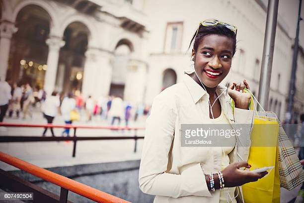 Young African European woman using wifi connection at Duomo Squa