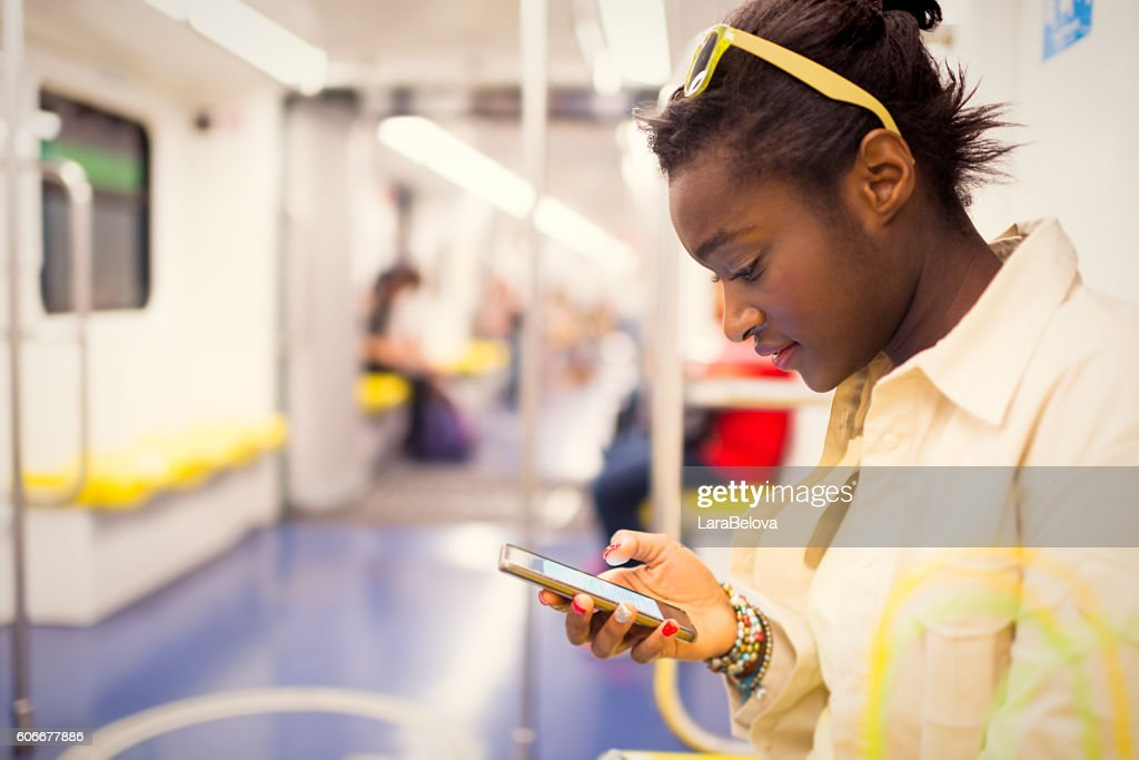 Young African European woman using wifi connection in subway tra : Stock-Foto