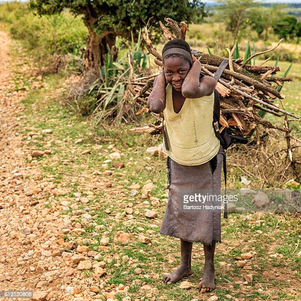 Young African girl carrying brushwood, southern Kenya, East Africa