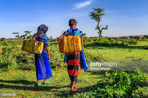 Young African girls carrying water from the well, Ethiopia, Africa