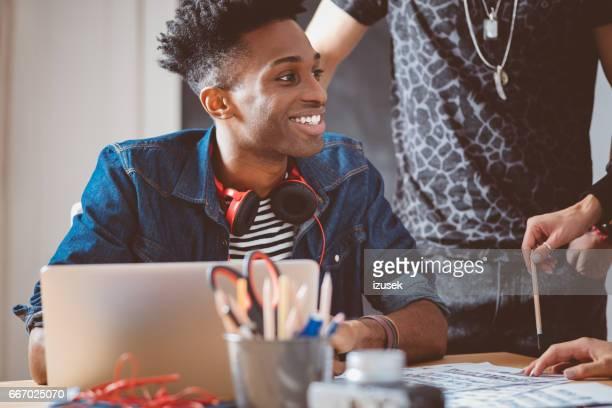 junge afrikanische mann in treffen mit kreativ-team - izusek stock-fotos und bilder