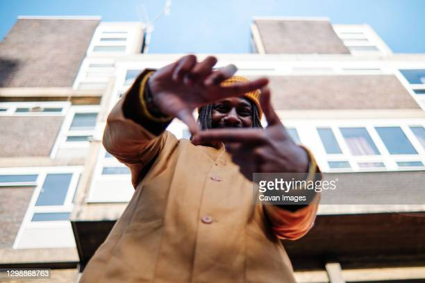 young african guy looking at camera, smiling through finger frame while standing in front of a building - innovation stock pictures, royalty-free photos & images