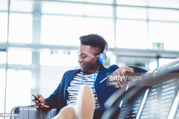 Young african guy waiting for flight at airport lounge