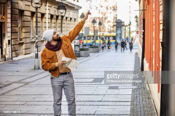 young african is walking in the city and exploring the sights using a map. - individual event stock pictures, royalty-free photos & images